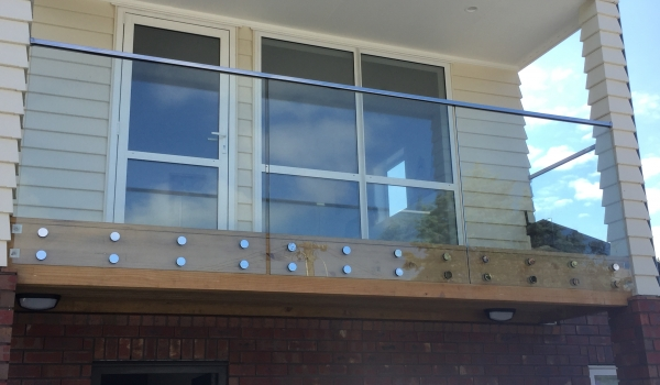 Glass balustrade with top rail and metal discs.